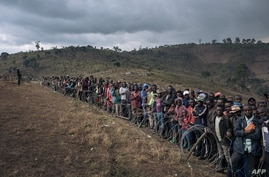 Displaced persons attend a visit by Congolese Defense Minister Aimé Ngoy Mukena (not visible) to the internally displaced…