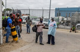 A nurse working for the National Health Department escorts a travellers to get a COVID-19 PCR test done before entering South…