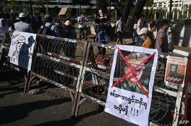 A poster featuring army chief Senior General Min Aung Hlaing is displayed on a barricade as protesters take part in a…