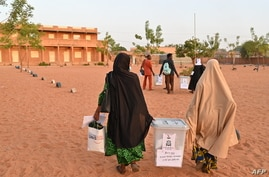 Election workers arrive with ballot boxes at the polling station during Niger's presidential election run off, in Niamey on…