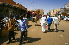 People walk in front of shops at a market in the Sudanese capital Khartoum on February 21, 2021. - Sudan said today it was…