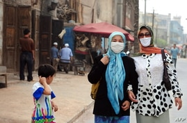 Uighur Muslim women wear headscarves and facemasks while walking on a street in the old town section of Kashgar on June 14,…