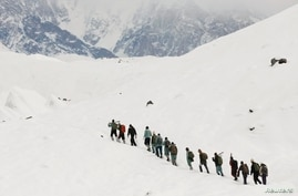 A group of Pakistani soldiers carry their guns uphill along the K2 base camp trek in the Karakoram mountain range in Pakistan…