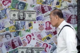 A man walks past an advertisement promoting China's renminbi (RMB) or yuan, U.S. dollar and Euro exchange services at foreign…