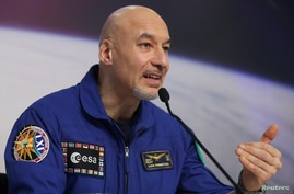 Italian ESA astronaut Luca Parmitano addresses a news conference after returning from commanding the International Space…