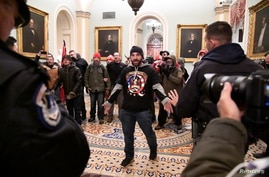 Trump supporter Douglas Austen Jensen, wearing a QAnon shirt, confronts police on the second floor of the U.S. Capitol after breaching security defenses, in Washington, January 6, 2021.