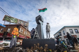Artists and community members help erect a new fist statue made of steel, to replace the old one, in the square where George…