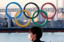 FILE - A man wears a protective mask amid the coronavirus (COVID-19) outbreak in front of the giant Olympic rings in Tokyo.