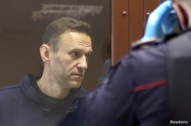 Kremlin critic Alexei Navalny, who is accused of slandering a Russian World War Two veteran, stands inside a defendant dock…