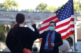 A USCIS employee swears in an immigrant in a socially-distanced outdoor naturalization ceremony to become a new U.S. citizen,…
