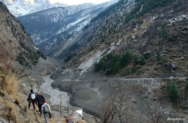 People walk past a destroyed dam after a Himalayan glacier broke and crashed into the dam at Raini Chak Lata village in Chamoli…