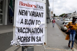 A woman walks past newspaper billboards during the coronavirus disease (COVID-19) outbreak in Johannesburg, South Africa,…
