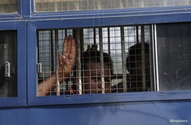 A man flashes the three-finger salute after being arrested during a protest against the military coup in Mawlamyine, Myanmar…