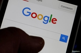 FILE PHOTO: A man holds his smartphone which displays the Google home page, in this picture illustration taken in Bordeaux,…