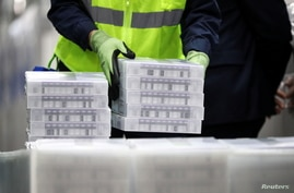 Pfizer employees handle containers of vaccine as U.S. President Joe Biden tours a Pfizer manufacturing plant producing the…