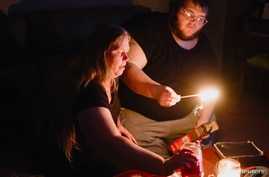 "Christina Beverly and John Shearon light candles in their home after winter weather caused electricity blackouts and ""boil…"