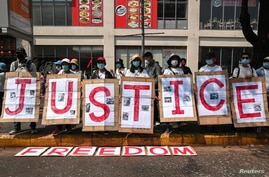 "People hold placards to form the word ""Justice"" during a protest against the military coup in Yangon, Myanmar, February 22,…"