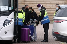 "A traveler is assisted by security outside the Novotel at Heathrow Airport, as Britain introduces a hotel quarantine programme for arrivals from a ""red list"" of 30 countries due to the coronavirus disease (COVID-19) pandemic, in London, Feb. 25, 2021."