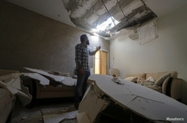 Mohamed Fahim inspects his house that was damaged by an intercepted missile in the aftermath of what Saudi-led coalition said…