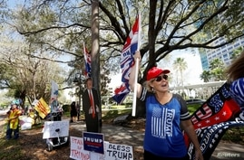 Former U.S. President Donald Trump supporter Kelly Fitzer waves a flag outside of the Conservative Political Action Conference (CPAC) in Orlando, Florida, U.S. Feb. 28, 2021.