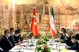 Turkish Foreign Minister Mevlut Cavusoglu, left, and Iran's Foreign Minister Mohammad Javad Zarif, second right, wearing face masks to protect against the coronavirus, speak during a meeting, in Istanbul, Monday, June 15, 2020. The two discussed the bilateral issues and Syria. (Turkish Foreign Ministry via AP, Pool)