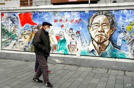 "Residents wearing masks past by a mural titled ""Memories""on the eve of the anniversary of the 76-day lockdown in the central…"