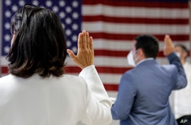 FILE- In this July 2, 2020, file photo, people take the oath of citizenship during a naturalization ceremony at U.S…