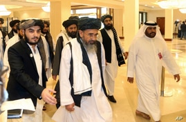 FILE - In this Sept. 12, 2020 photo, a Taliban delegation arrive to attend the opening session of the peace talks between the…