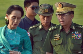 FILE - Aung San Suu Kyi, left, Myanmar's foreign minister, walks with senior General Min Aung Hlaing
