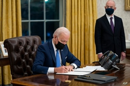 Secretary of Homeland Security Alejandro Mayorkas looks on as President Joe Biden signs an executive order on immigration, in…