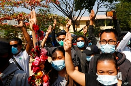 Supporters show a three-finger salute of protest while four arrested activists make a court appearance in Mandalay, Myanmar,…