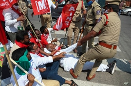 Policemen detain activists of various organizations as they block a highway during a nationwide shutdown called by thousands of Indian farmers protesting new agriculture laws in Hyderabad, India, Feb. 6, 2021.