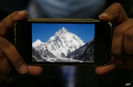 A photo of K2, the world's second-highest mountain, is displayed on a cell phone in Islamabad, Pakistan, Feb. 9, 2021.