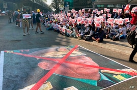 A large image that has an X mark on the face of Commander in chief Senior Gen. Min Aung Hlaing, also chairman of the State Administrative Council, lies on a road as anti-coup protesters gather outside the Hledan Centre in Yangon, Myanmar, Feb. 14, 2021.
