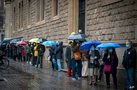 People line up outside a polling station, before casting their vote for the regional Catalan election in Barcelona, Spain, Feb. 14, 2021.