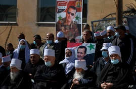 Druse supporters of Syrian President Bashar Assad display display pictures of him during a rally close to the Syrian border demanding the return of the Golan Heights, captured by Israel in 1967,  in Majdal Shams, Golan Heights, Feb. 14, 2021.