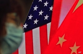 A woman wearing a face mask sits near a screen showing China and U.S. flags as she listens to a speech by Chinese Foreign Minister Wang Yi at the Lanting Forum on bringing China-U.S. relations, Beijing, Feb. 22, 2021.