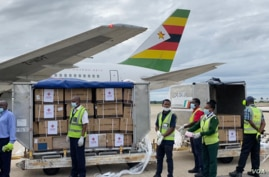 Health officials guard Zimbabwe's donation of 200,000 Sinopharm COVID-19 vaccine doses, which arrived at the Robert Gabriel Mugabe International Airport in Harare on Feb. 15, 2021. The vaccines were a donation by Beijing. (Columbus Mavhunga/VOA)