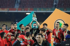 Morocco's coach Houcine Ammouta (C) holds up the trophy after his team's win during the African Nations Championship (CHAN) final football match between Morocco and Mali at Stade Ahmadou Ahidjo in Yaounde, Cameroon, Feb. 7, 2021.