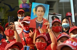 Myanmar migrants hold up portraits of detained leader Aung San Suu Kyi as they rally outside Myanmar's embassy in Bangkok, Thailand, Feb. 1, 2021.