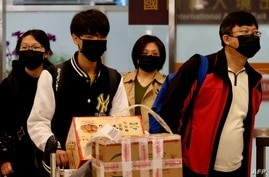 FILE - Passengers wearing masks to protect against the coronavirus arrive at Sungshan Airport, in Taipei, Taiwan, Jan. 22, 2020. Many Taiwanese who had lived abroad have returned home, feeling safer there from the pandemic's reach.