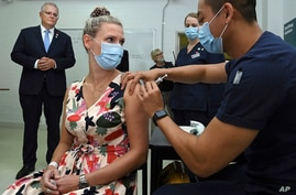 Australian Prime Minister Scott Morrison, left, watches as Sarah Fletcher receiving a vaccine at the Sydney local health district vaccination hub in Sydney, Feb. 19, 2021.