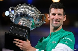 Serbia's Novak Djokovic holds the Norman Brookes Challenge Cup after defeating Russia's Daniil Medvedev in the men's singles final at the Australian Open tennis championship in Melbourne, Feb. 21, 2021.