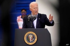 In an image taken through scaffolding, President Joe Biden speaks during a trip to Housten, Texas, Feb. 26, 2021.