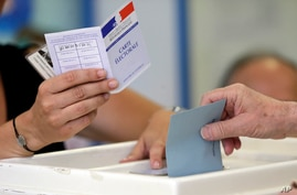 FILE - A man casts his ballot in parliamentary elections at a polling station in Marseille, southern France, June 18, 2017.