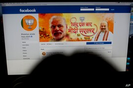 FILE - A woman checks the Facebook page of India's ruling Bharatiya Janata Party, in New Delhi, March 26, 2019.