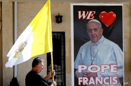 A Christian priest holds a Vatican flag as he walks past a poster of Pope Francis during preparations for the Pope's visit in Mar Youssif Church in Baghdad, Iraq, Feb. 26, 2021.