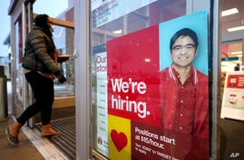 A passer-by walks past an employment hiring sign at a Target store, Feb. 9, 2021, in Westwood, Massachusetts.