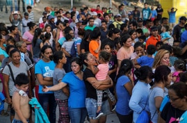 "Migrants, many of whom were returned to Mexico under the Trump administration's ""Remain in Mexico"" policy, wait in line to get a meal in an encampment near the Gateway International Bridge in Matamoros, Mexio, Aug. 30, 2019."