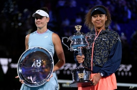 Japan's Naomi Osaka, right, holds the Daphne Akhurst Memorial Cup defeating American Jennifer Brady, left, in the women's singles final at the Australian Open tennis championship in Melbourne, Australia, Feb. 20, 2021.